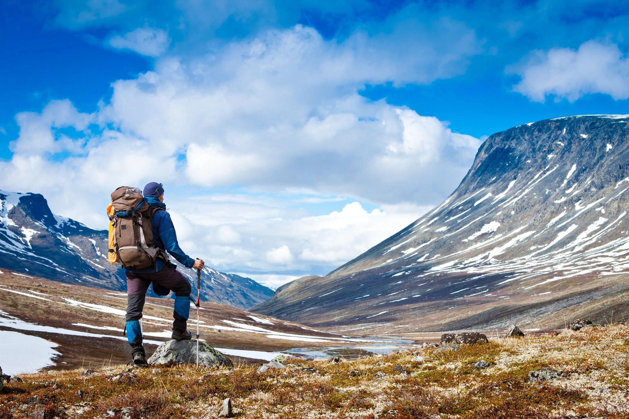 Stock photo of man with backpack hiking in mountains colorado